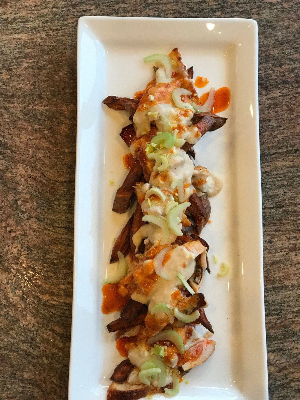 Sweet Potato Fries with Crispy Buffalo Chicken, topped with Blue Cheese Gravy.
