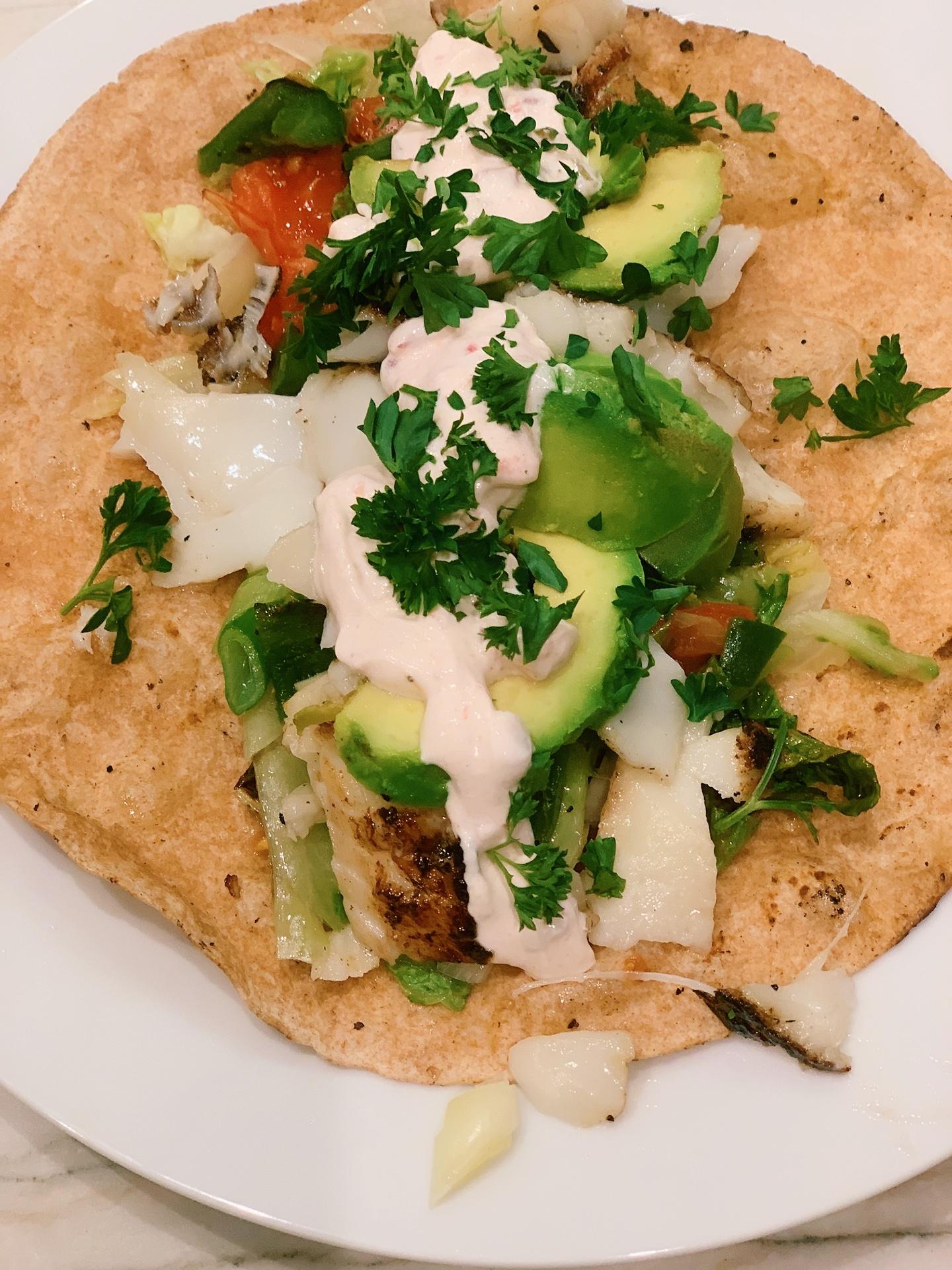 Fish in a soft tortilla with cilantro, crema, tomato, lettuce